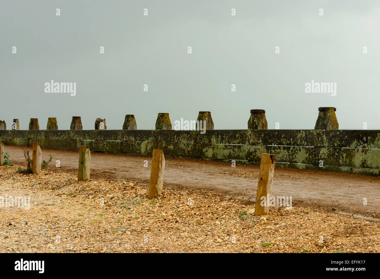 detail of foot path delimitation at shingle beach of touristic location, shot under bright cloudy sky - Stock Image