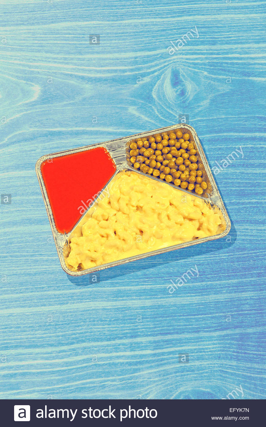 TV dinner kitsch fast food meal in aluminum tray on blue wood background - Stock Image