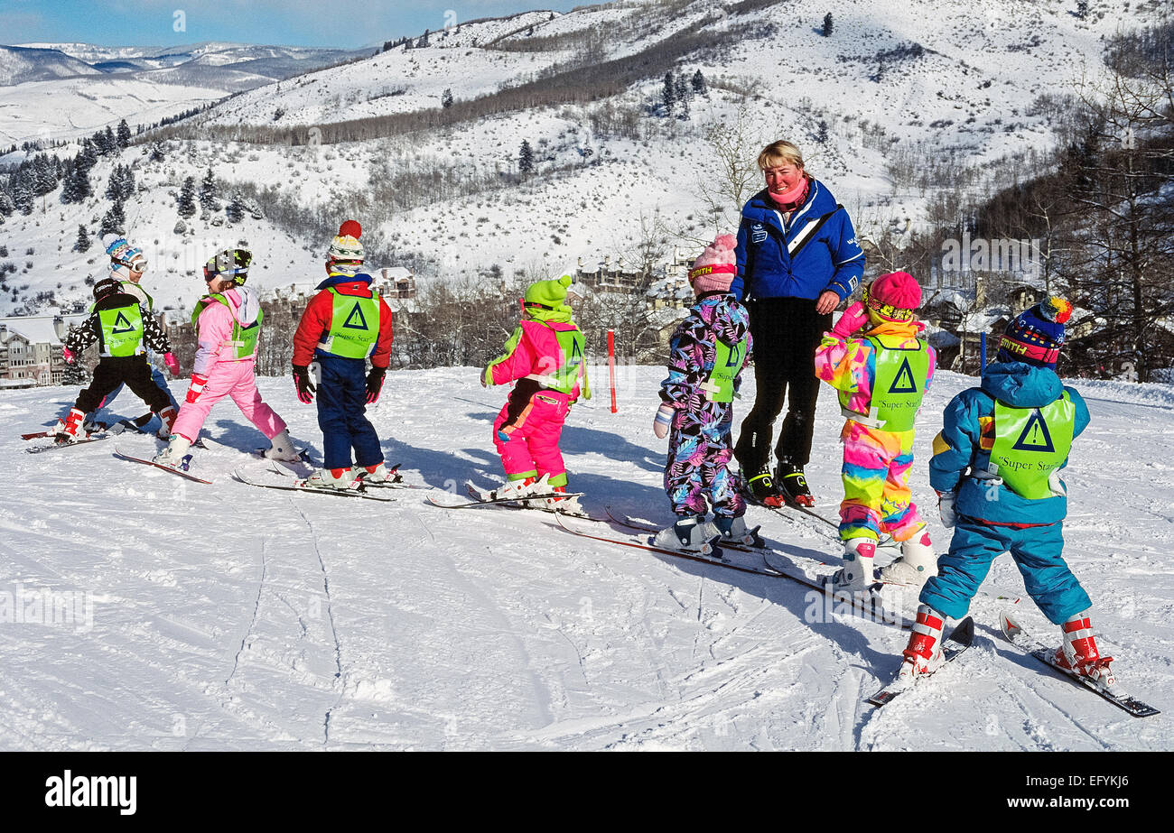 Eight young first-time skiers take a group lesson with a Beaver Creek Ski School instructor on a snowy slope in - Stock Image