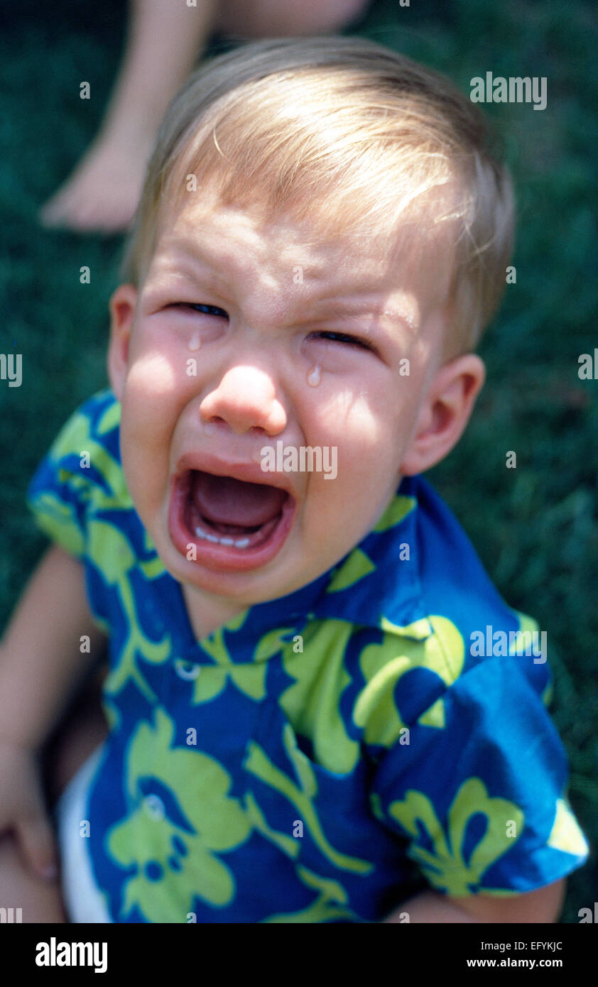 Two big tears drip from eyes of a crying young American baby boy whose mouth is wide open to scream his unhappiness - Stock Image