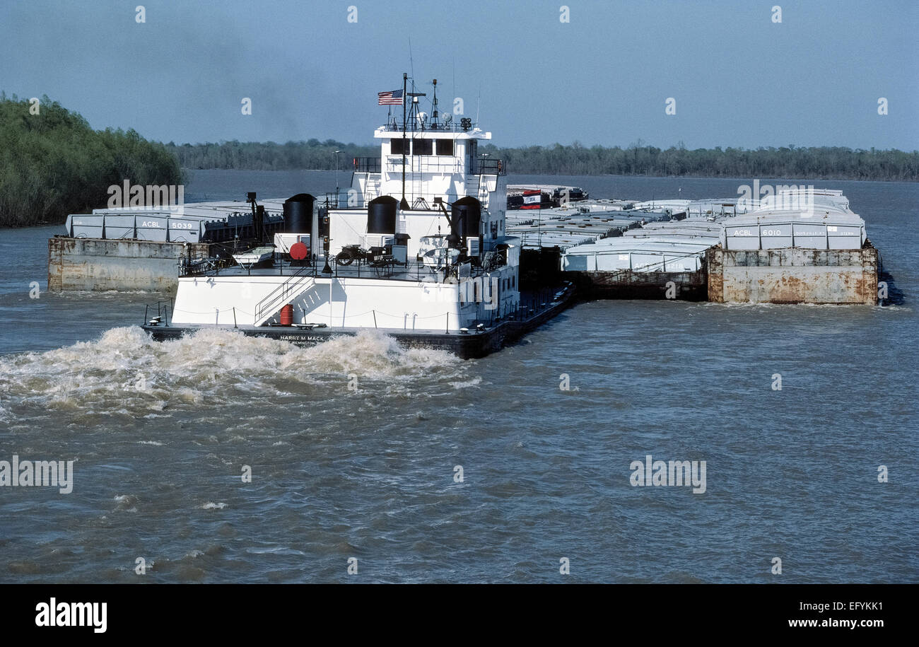 A powerful type of towboat called a pusher, pusher boat or pusher tug pushes full and empty cargo barges up the - Stock Image