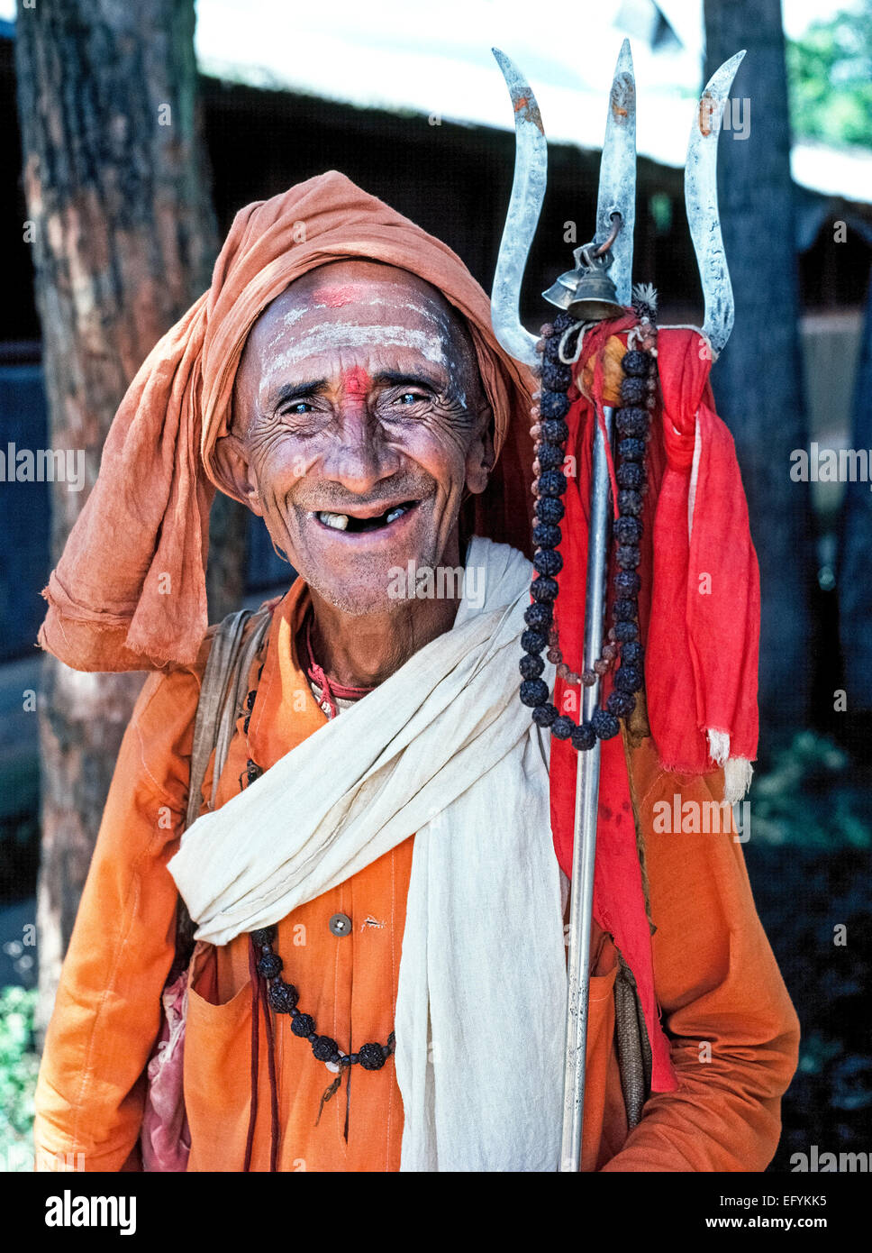 An elderly almost-toothless Hindu holy man in well-worn clothing holds a metal trident and smiles for tourists in - Stock Image