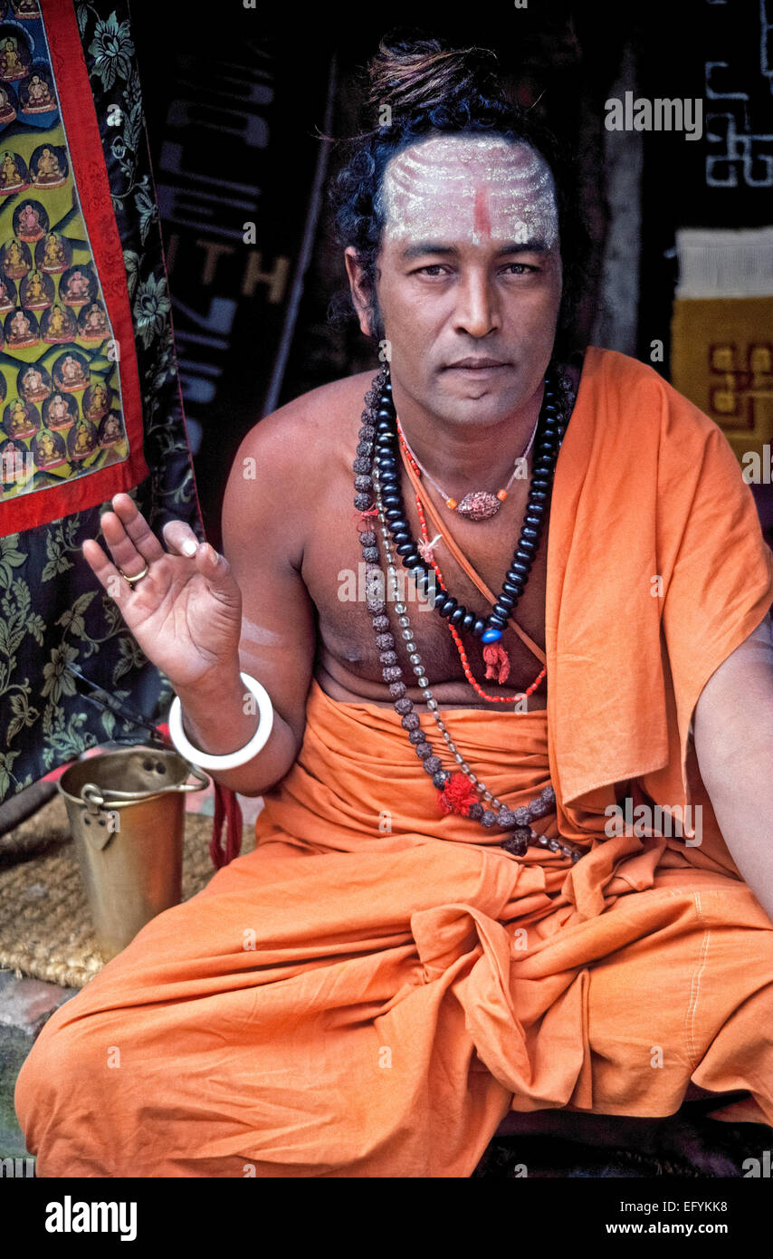 A younger holy man wearing saffron-colored clothing makes a spiritual hand gesture outside a Hindu temple in Kathmandu, - Stock Image