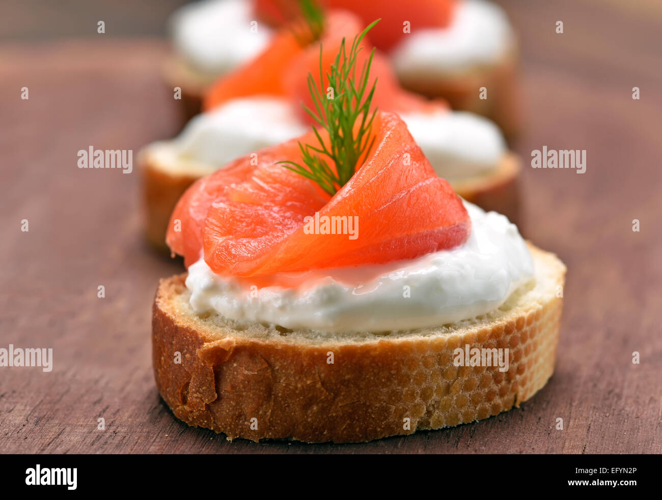 Sandwiches with salmon on wooden cutting board, close up view - Stock Image