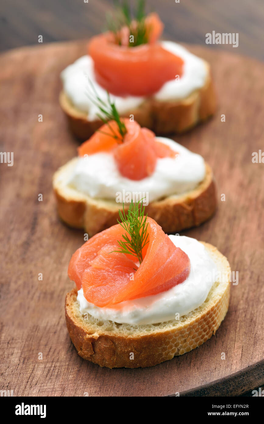 Sandwiches with salmon on wooden cutting board - Stock Image