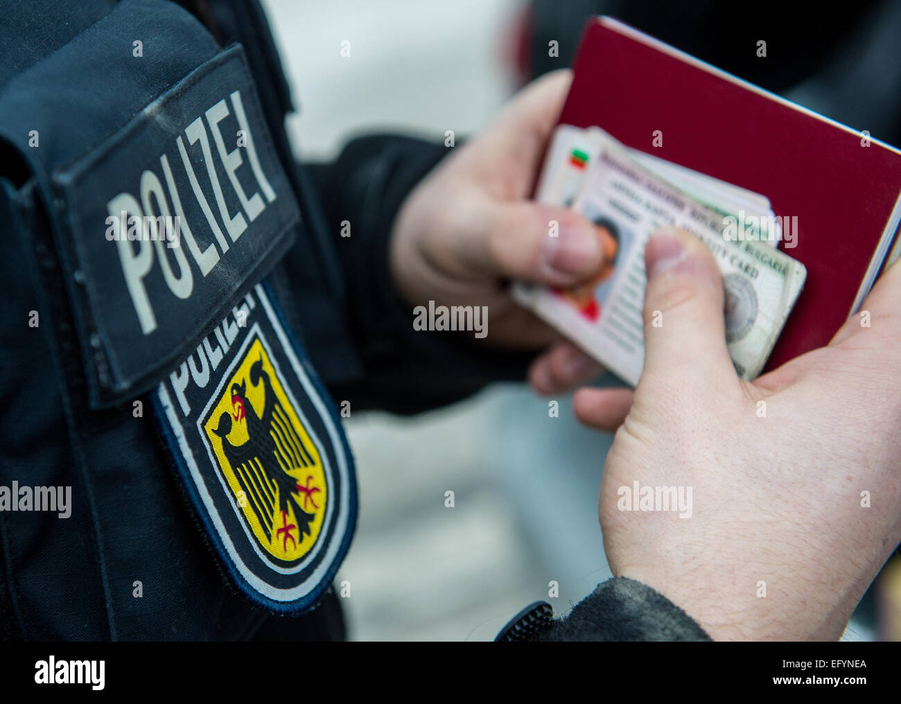 Passau, Germany. 12th Feb, 2015. An officer of the German federal police holds foreign ID-Cards in his hands during - Stock Image
