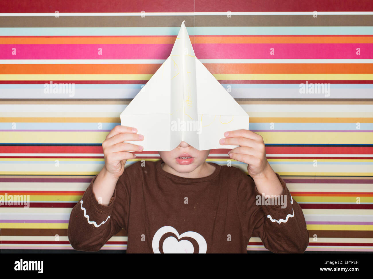 Child holding paper airplane in front of face Stock Photo