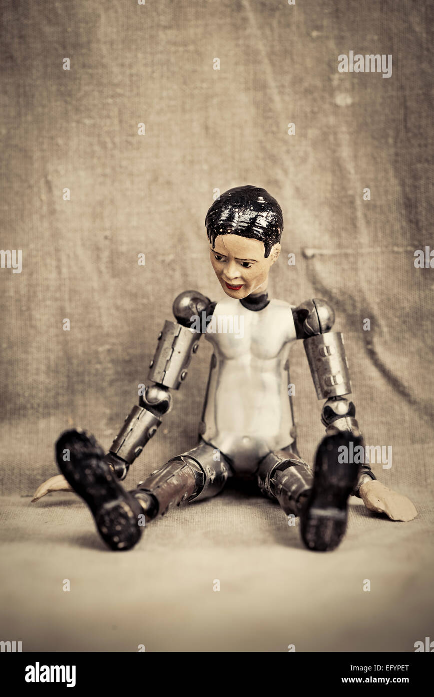 Pensive and depressed male toy doll sitting and looking down. Old fashioned retro design. - Stock Image
