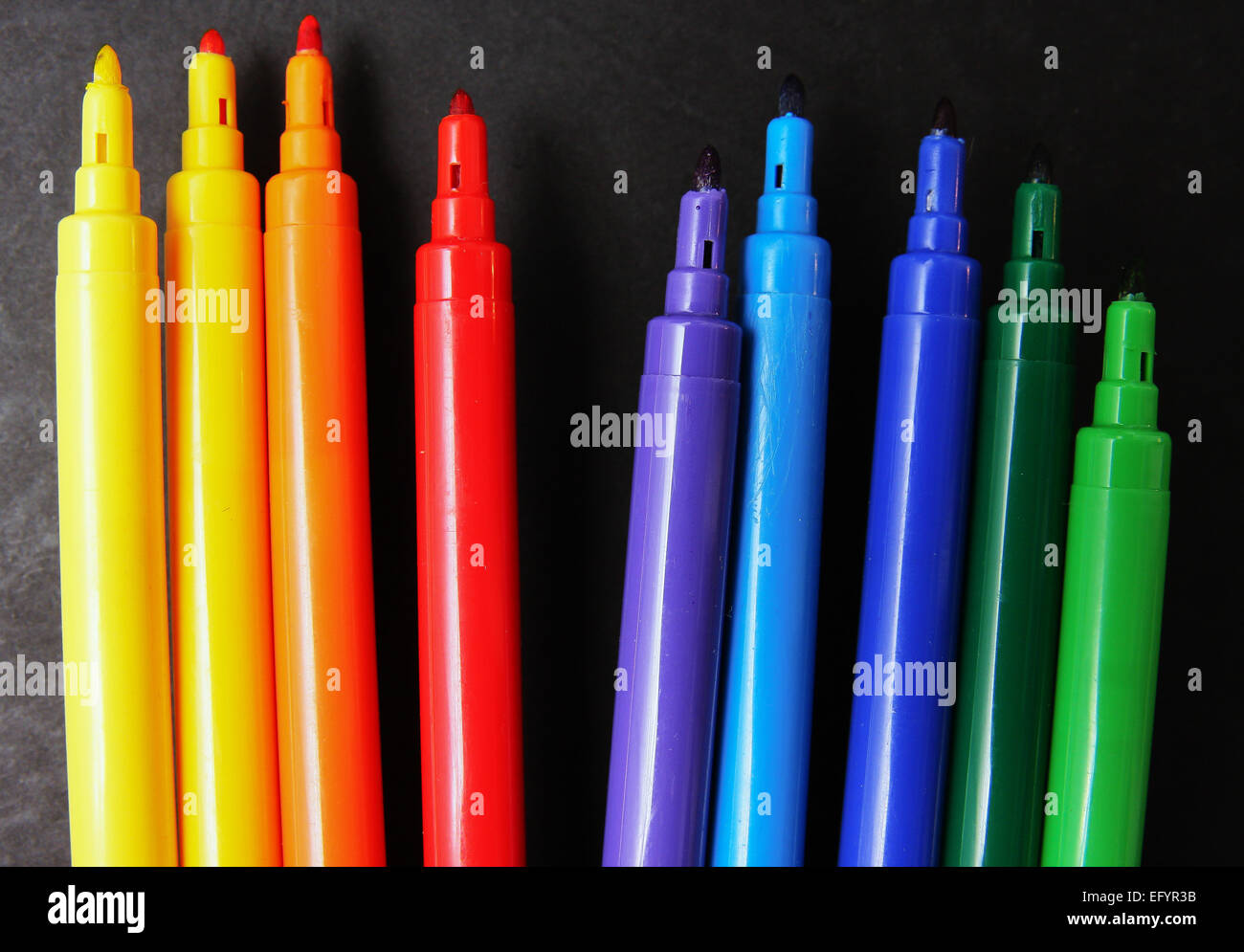 Row Of Colourful Pens On Black Background - Stock Image