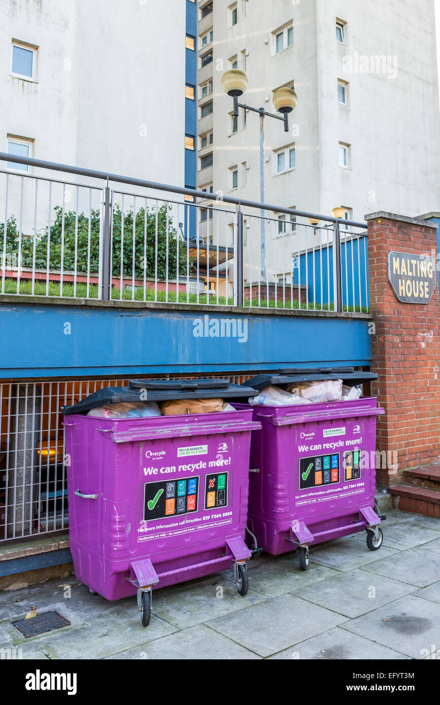 Rubbish bins outside The Malting House, a high rise block of flats in Poplar, East London, in the Borough of Tower - Stock Image