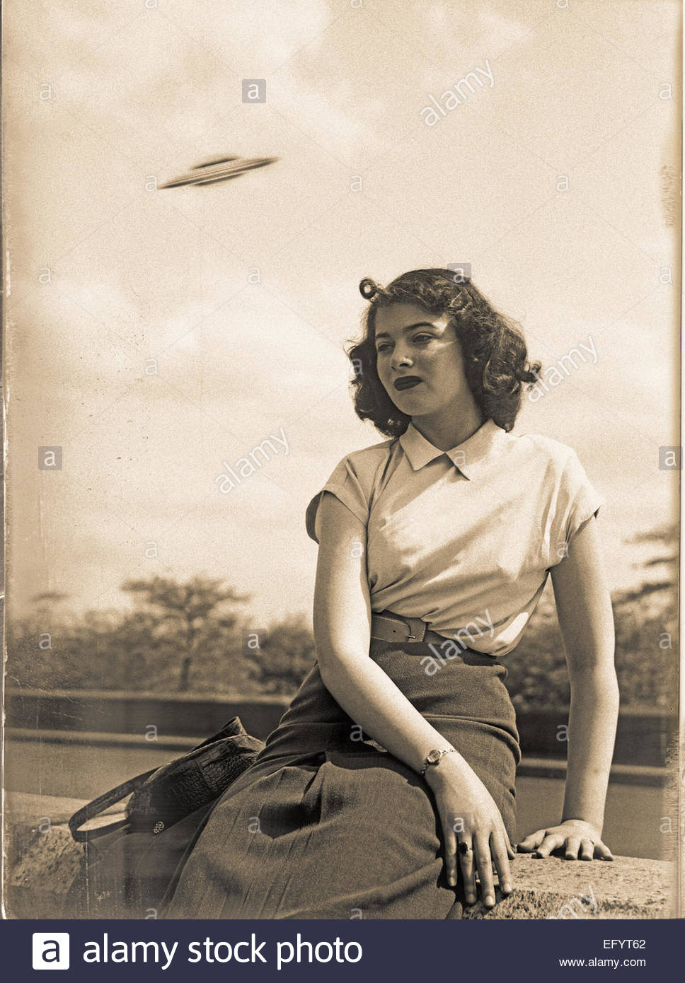 Vintage UFO snapshot of girl with flying saucer in background - Stock Image