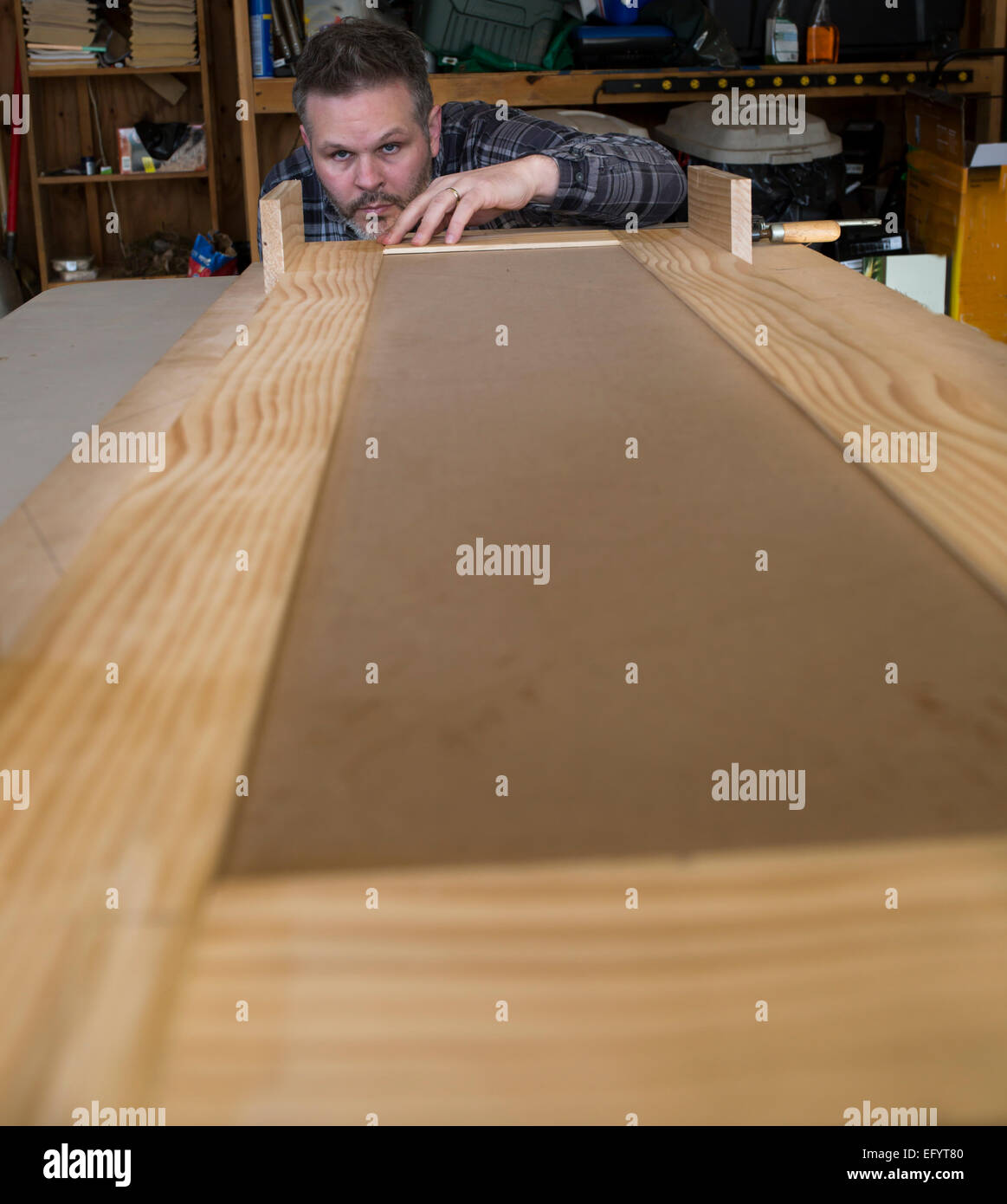 Man leaning down and measuring woodworking project - Stock Image