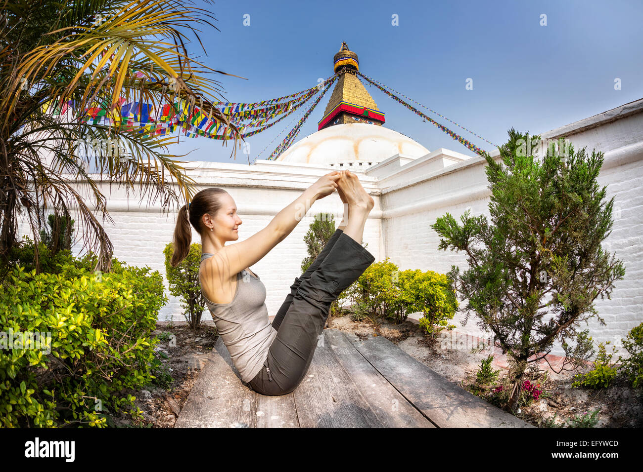 Woman doing yoga near Bodnath stupa, Kathmandu, Nepal - Stock Image
