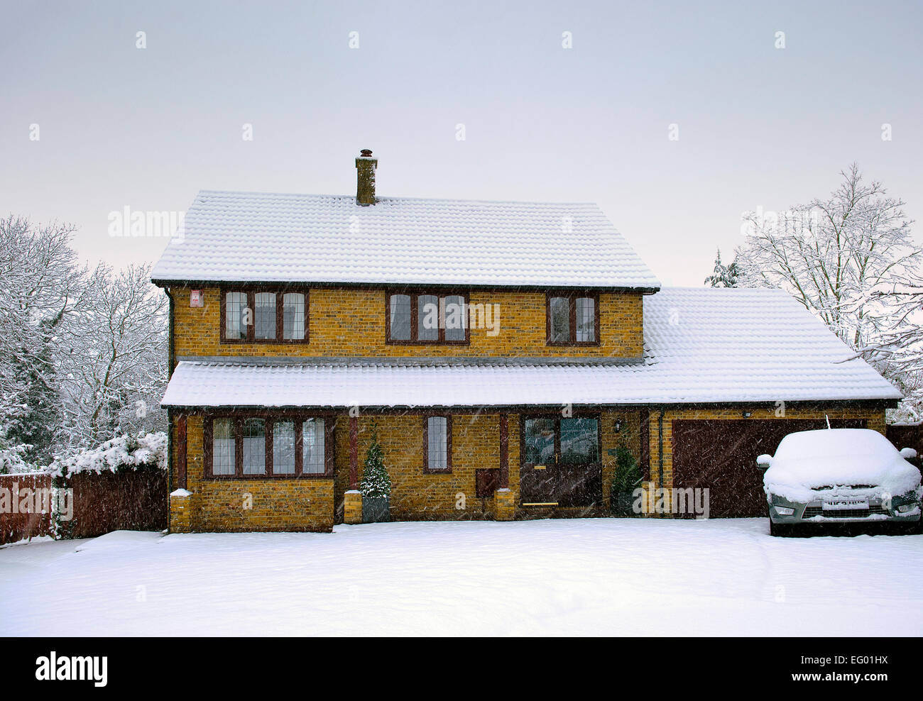 Day time image of large executive style detached house covered in snow Stock Photo