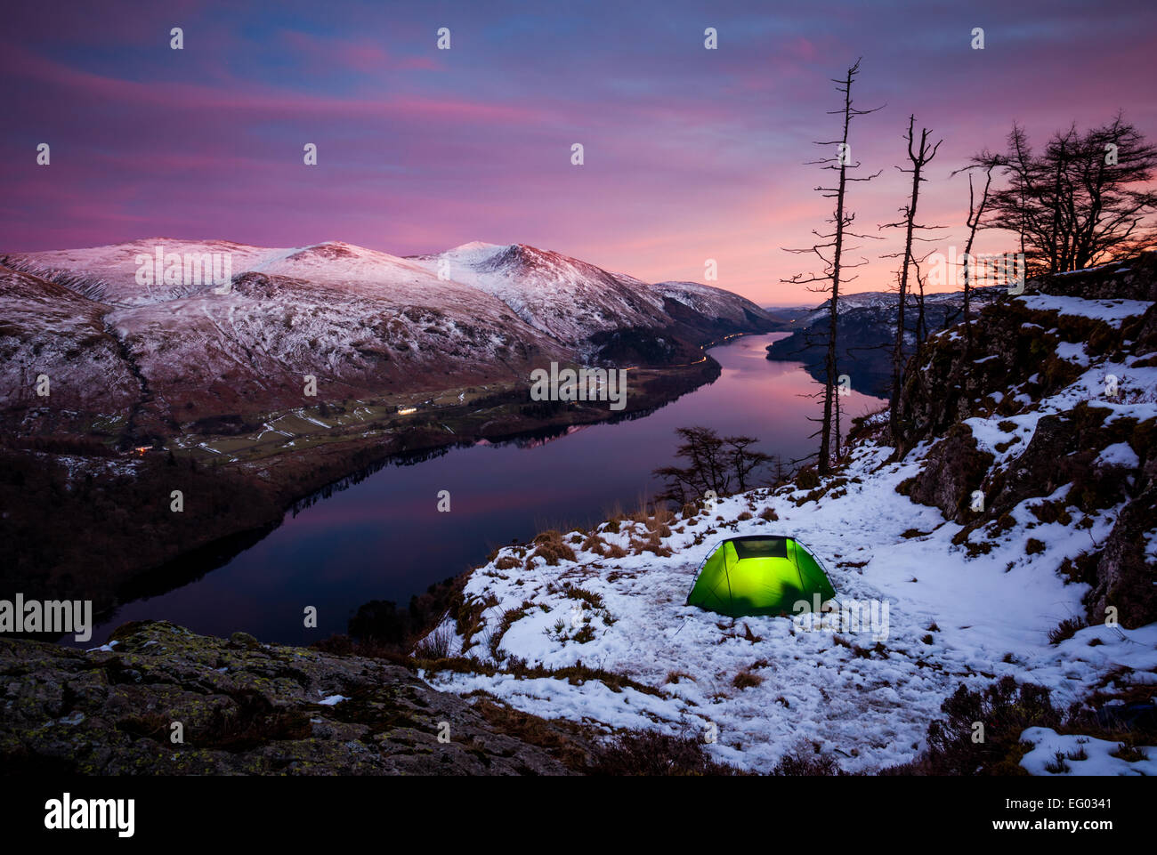Lit wild camp tent at twilight after a beautiful pink sunset at Raven Crag, Lake Thirlmere in the English Lake District. - Stock Image