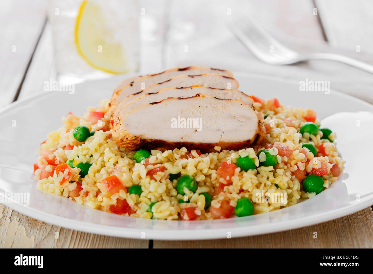 couscous with green peas and chicken fillet grill - Stock Image