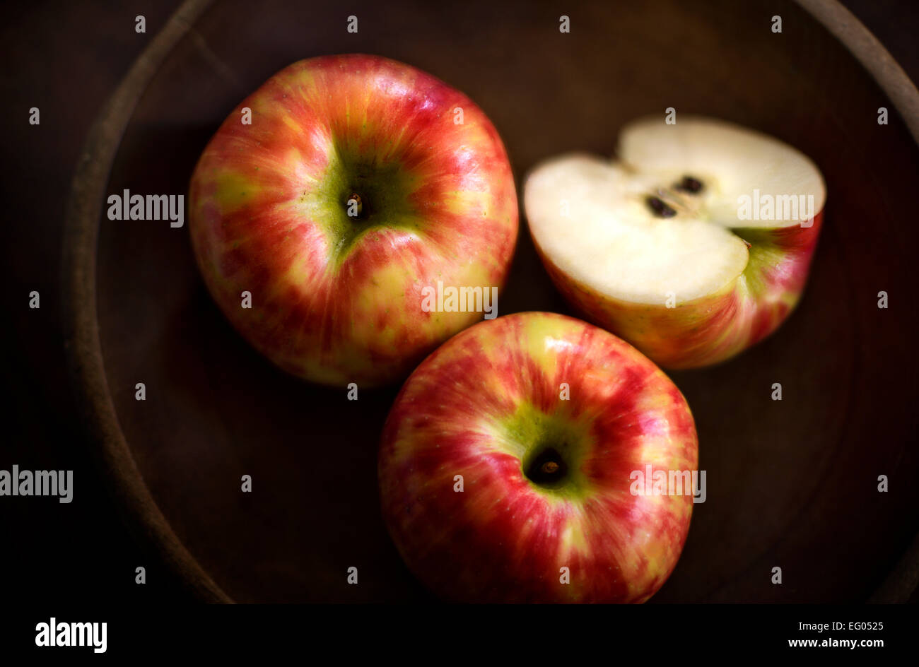Honeycrisp apples in a rustic wooden bowl. - Stock Image