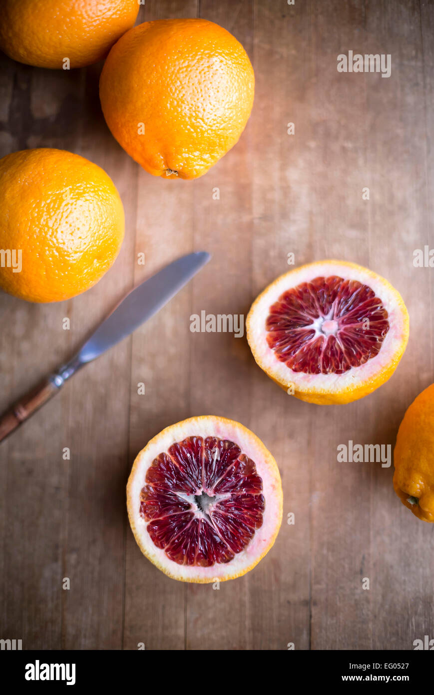 Blood oranges whole and sliced on a rustic wood cutting board with knife. - Stock Image