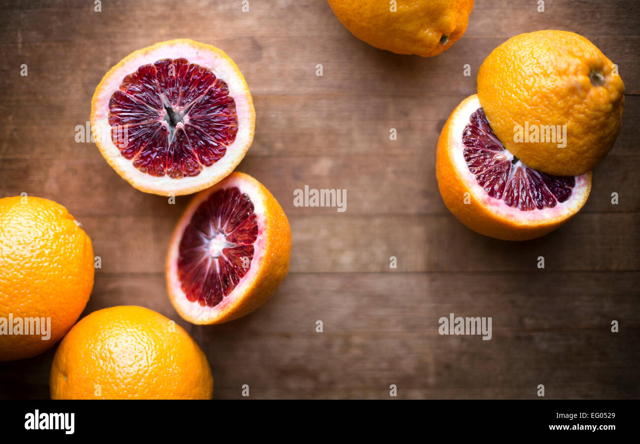 Blood oranges whole and sliced on a rustic wood cutting board. - Stock Image