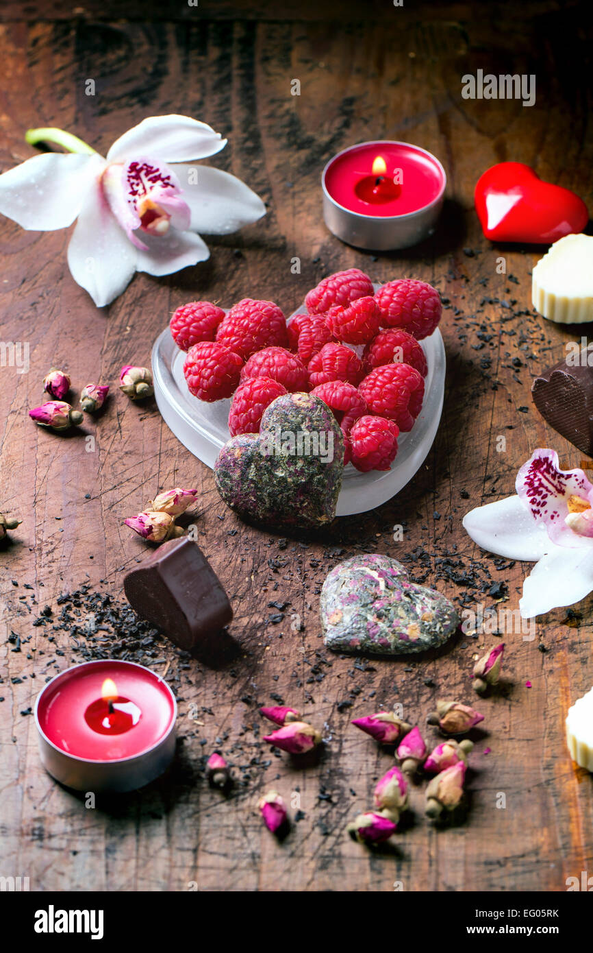 Chocolate candies heart shaped with dry tea roses, fresh raspberries and orchids for Valentine's Day. - Stock Image