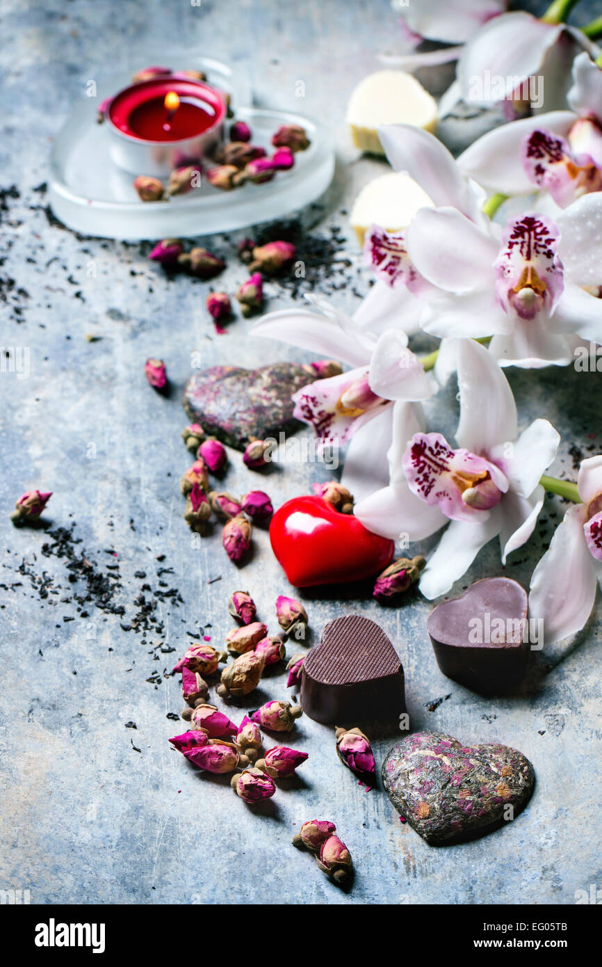 Chocolate candies heart shaped with dry tea roses and orchids for Valentine's Day. - Stock Image