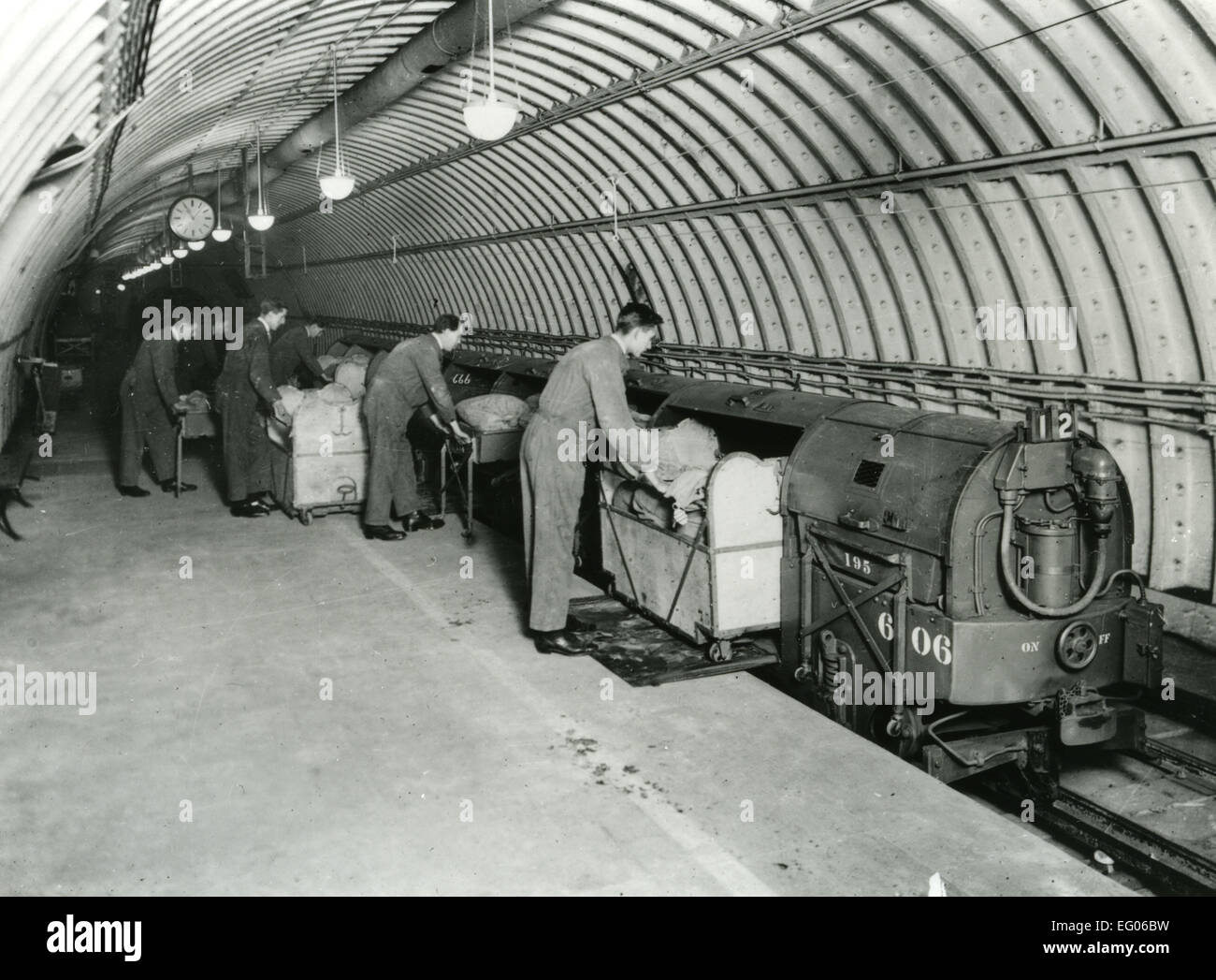 Photograph of the Post Office Railway . Several men are loading post onto train underground. It ran for 22 hours - Stock Image