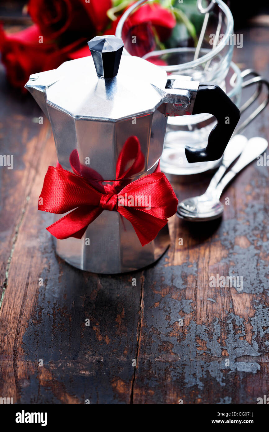 Valentine composition with coffee maker and flowers on wooden background - Stock Image