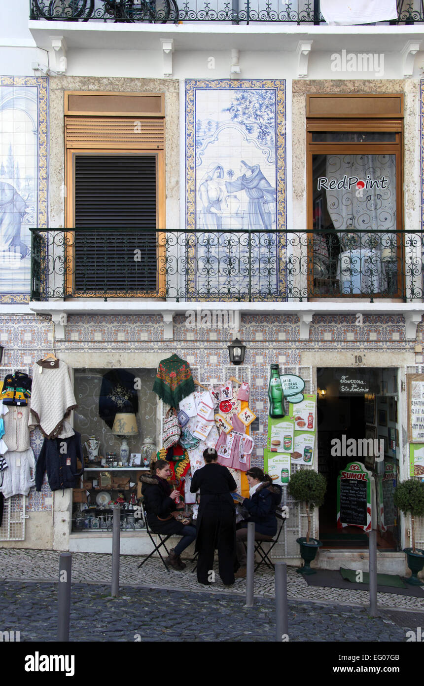 Tourists sitting outside a cafe in the popular sightseeing Alfama district of Lisbon in Portugal - Stock Image