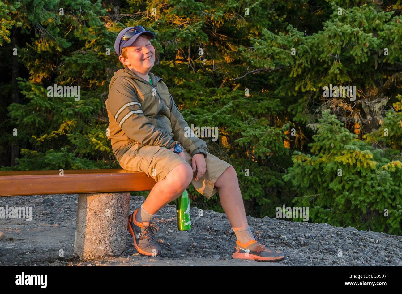 Boy laughing on bench - Stock Image