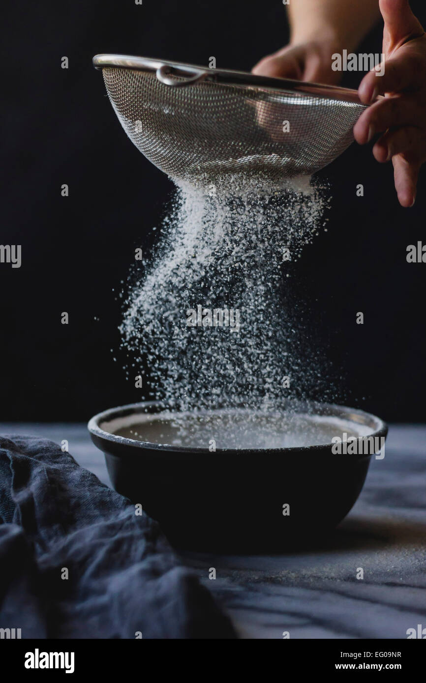 Sifting flour into a bowl whilst cooking Stock Photo