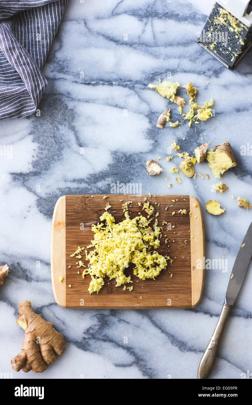 Grated ginger on a chopping board - Stock Image