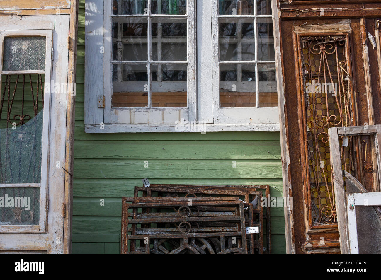 Display of old doors and iron grates against green painted outside wall of antique shop. & Display of old doors and iron grates against green painted outside ...