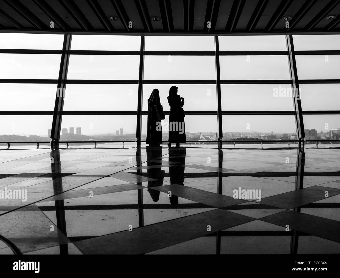 Silhouette of two Muslim women looking at the cityscape through glass walls - Stock Image