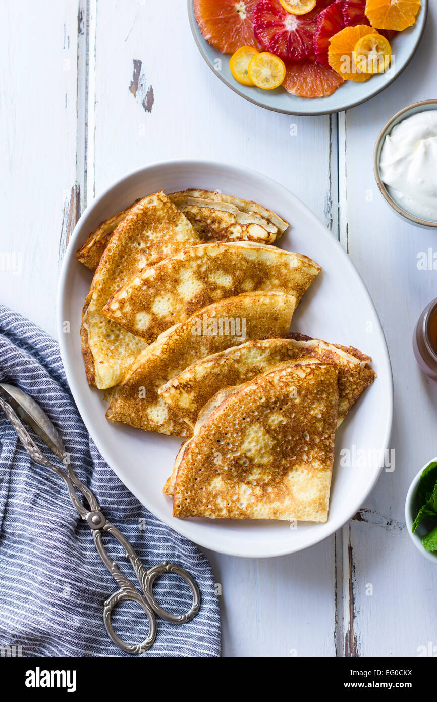 Crepes with a citrus fruit side. - Stock Image