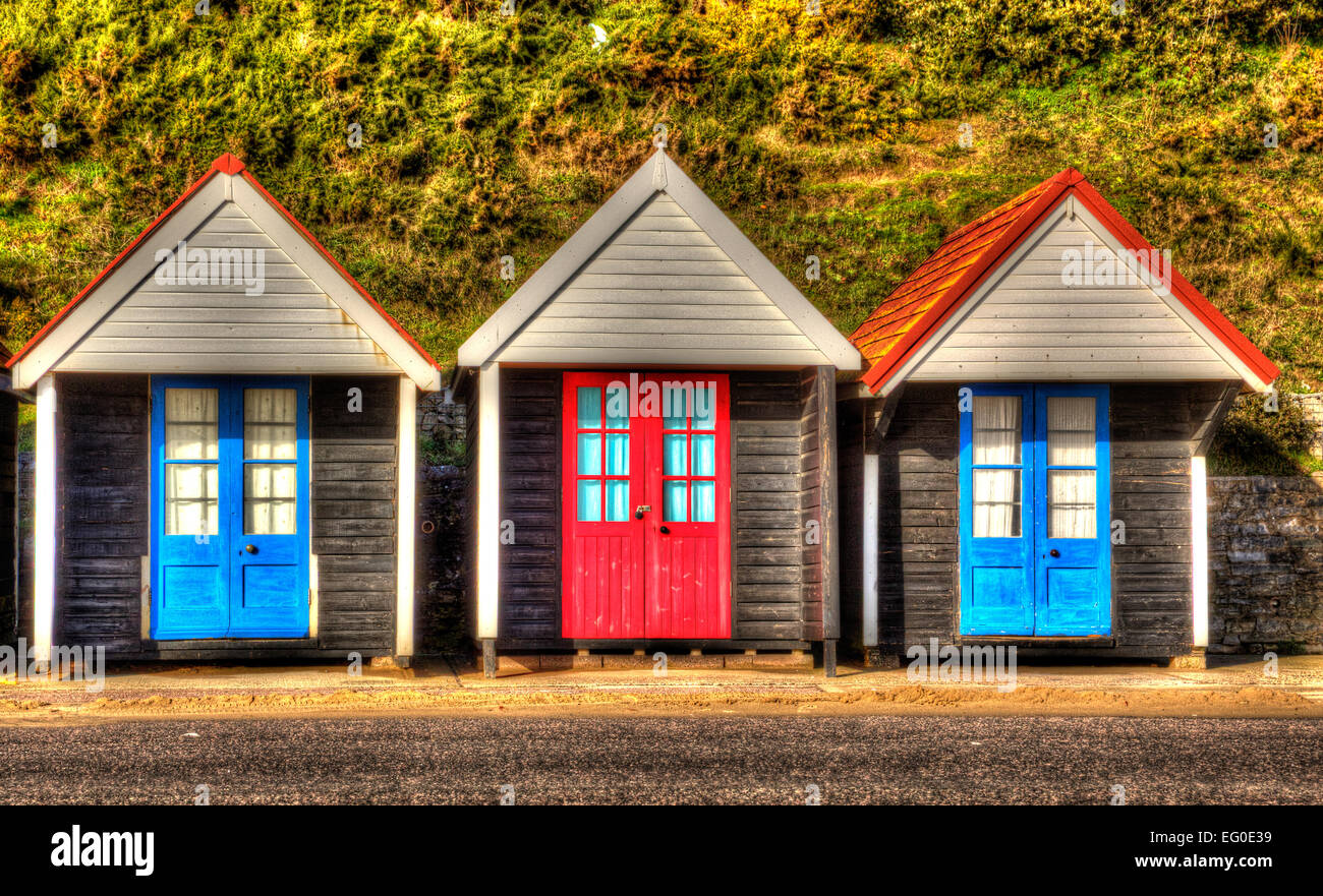 Beach huts with blue and red doors in a row traditional English structure and shelter found at the seaside in HDR - Stock Image