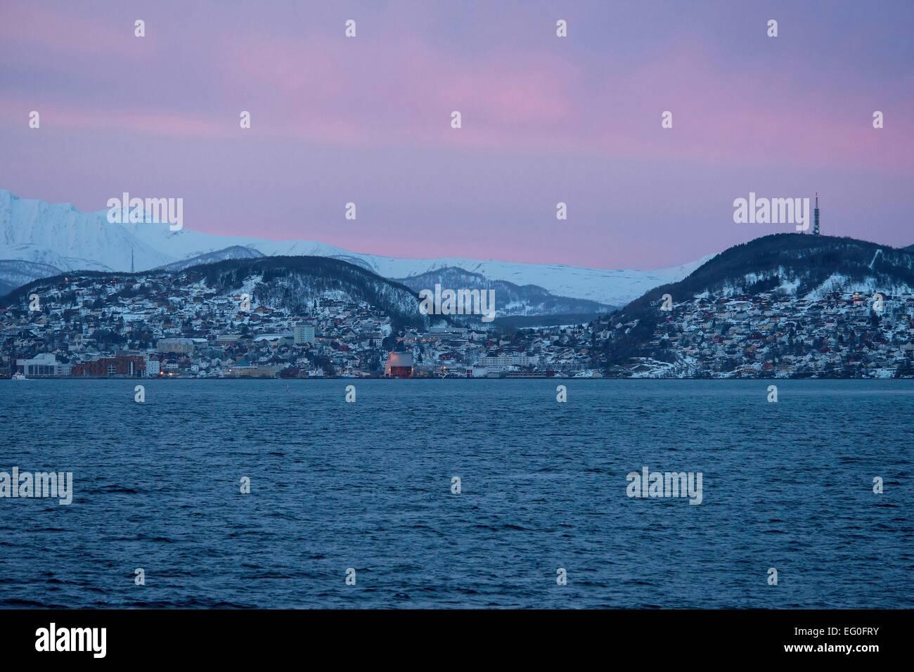 Stadt auf Hügeln am Vågsfjord, in der Ferne leuchten schneebedeckte Berge unter buntem Morgenhimmel; 26.02.2014 - Stock Image