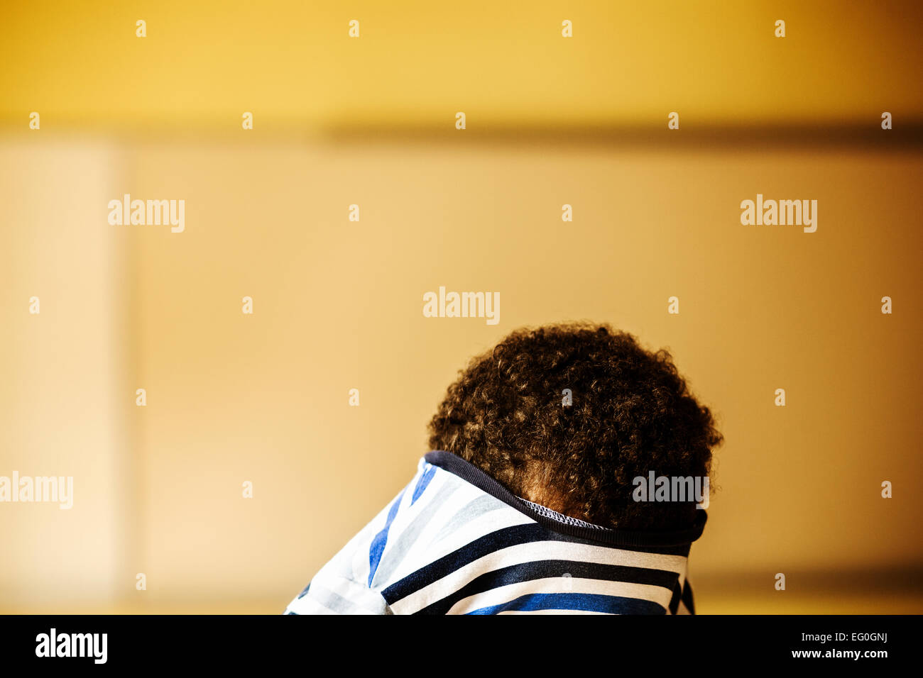 Mischievous boy hiding face in t-shirt at classroom Stock Photo