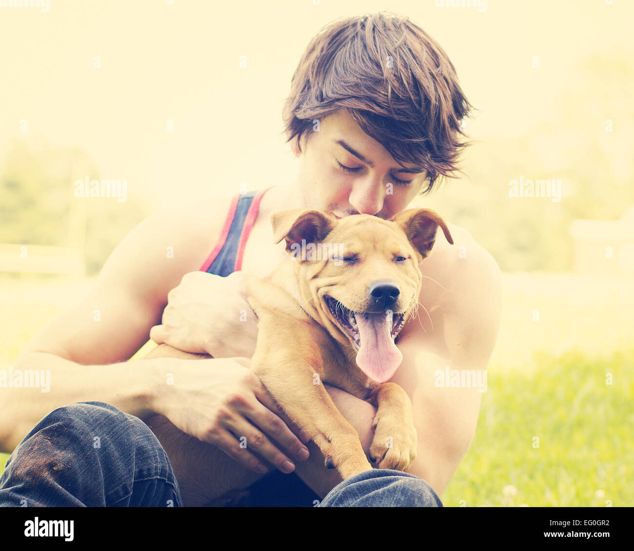 Young man holding puppy outdoors - Stock Image
