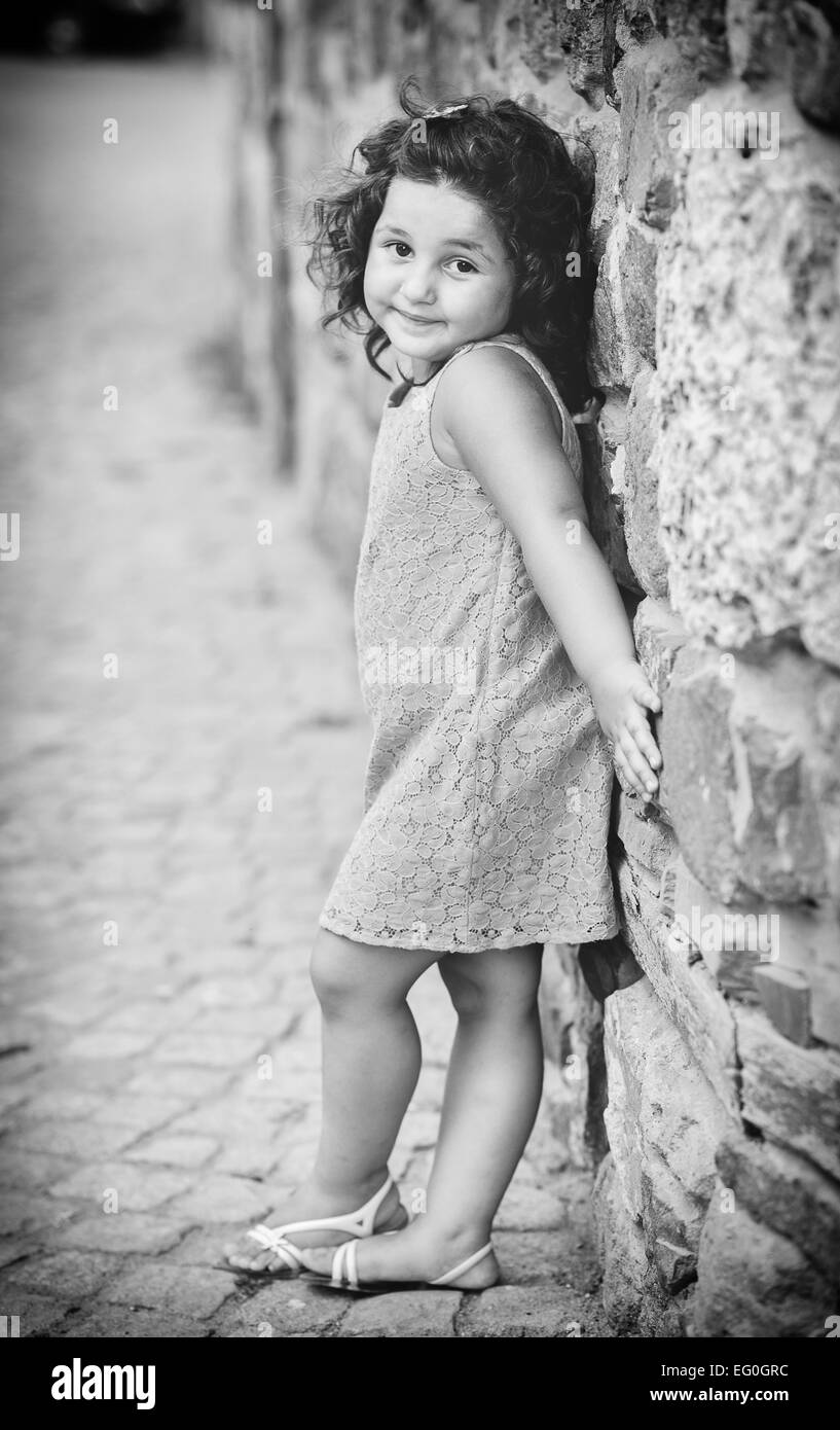 Small girl (4-5) backed against wall - Stock Image