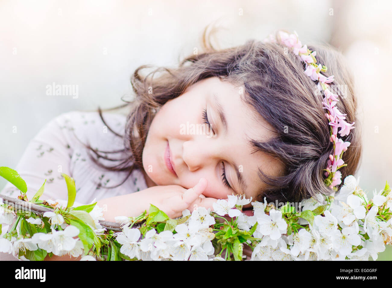 Cute girl (4-5) sleeping on flowers - Stock Image