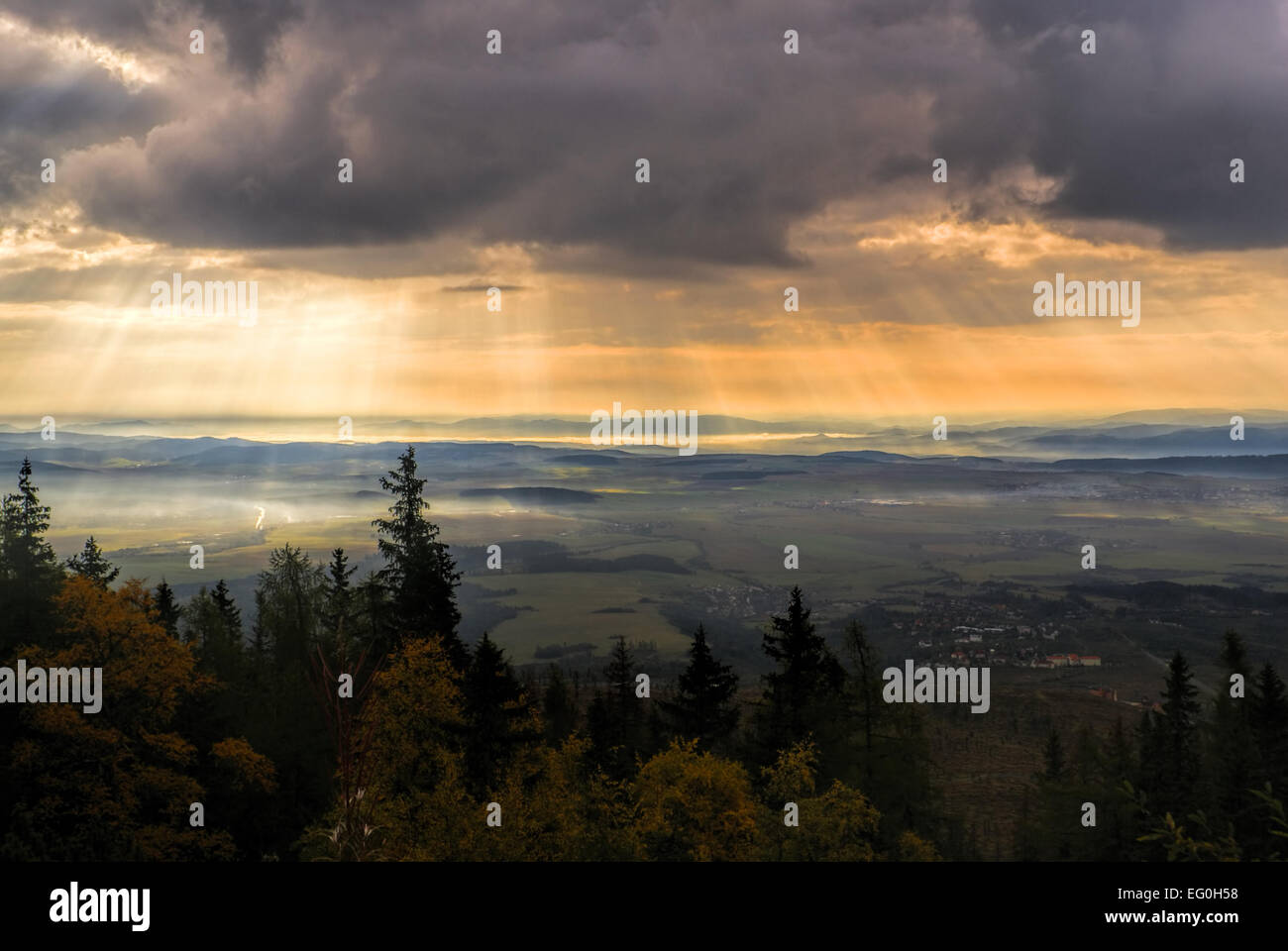 Godly light rays passing through clouds in the early morning above hilly countryside - Stock Image