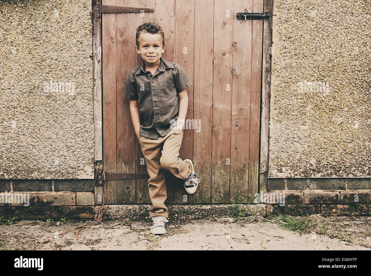 Portrait of boy in front of old stable at farm - Stock Image