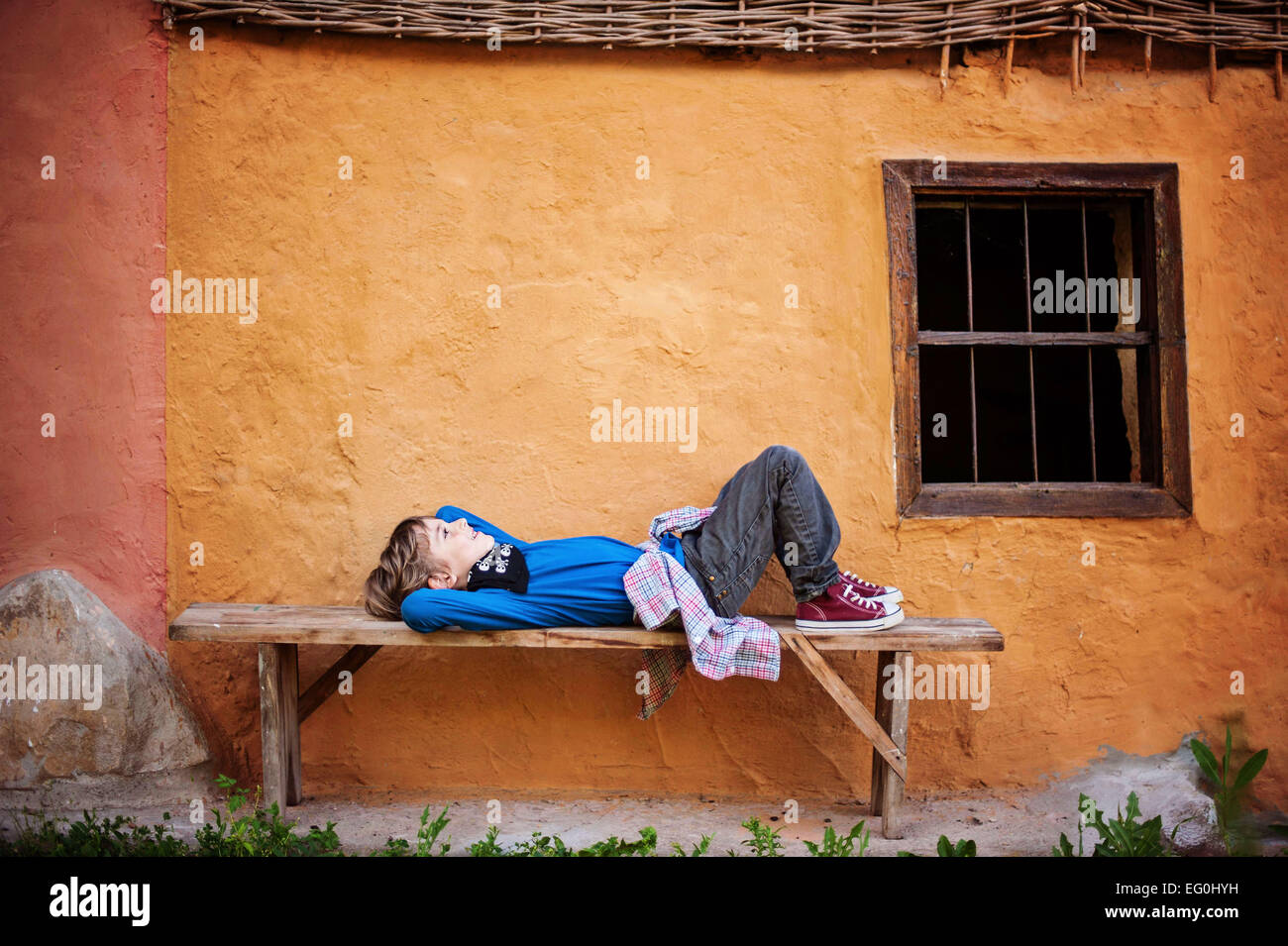 Boy (6-7) laying on bench - Stock Image