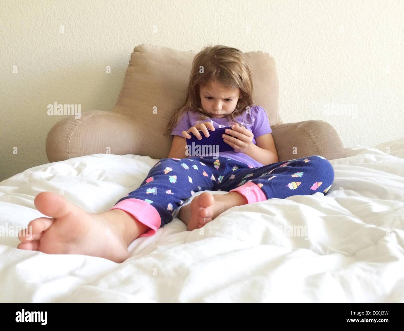 Girl (4-5) playing on smart phone - Stock Image