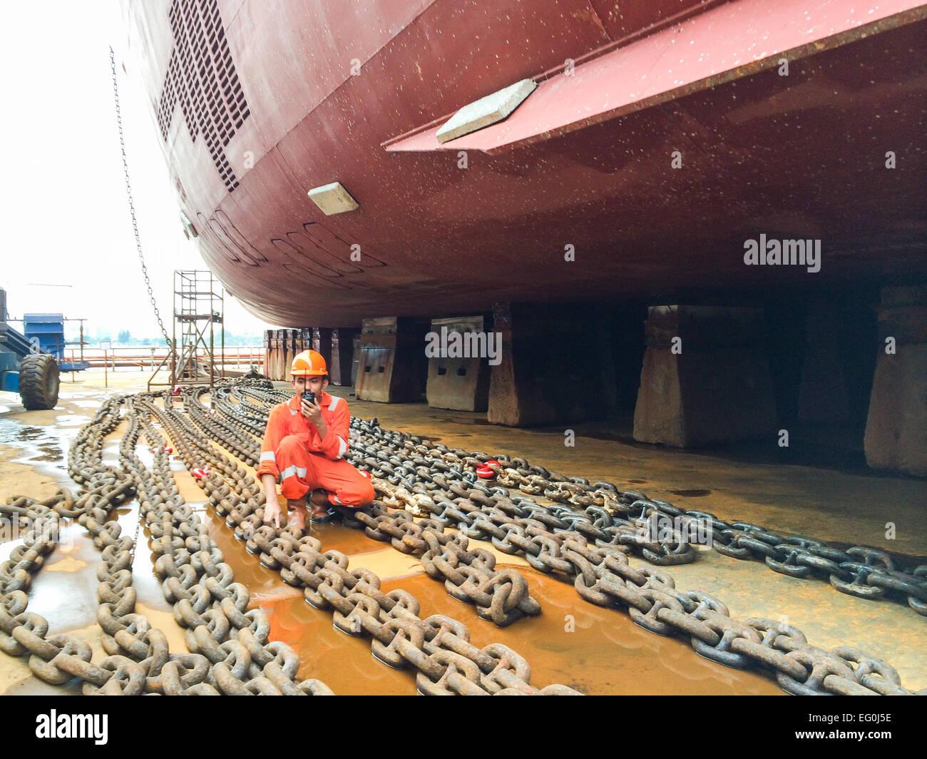 Dock worker in a shipyard talking on a walkie talkie - Stock Image