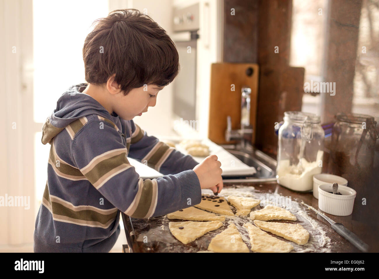 Boy (4-5) preparing meal - Stock Image