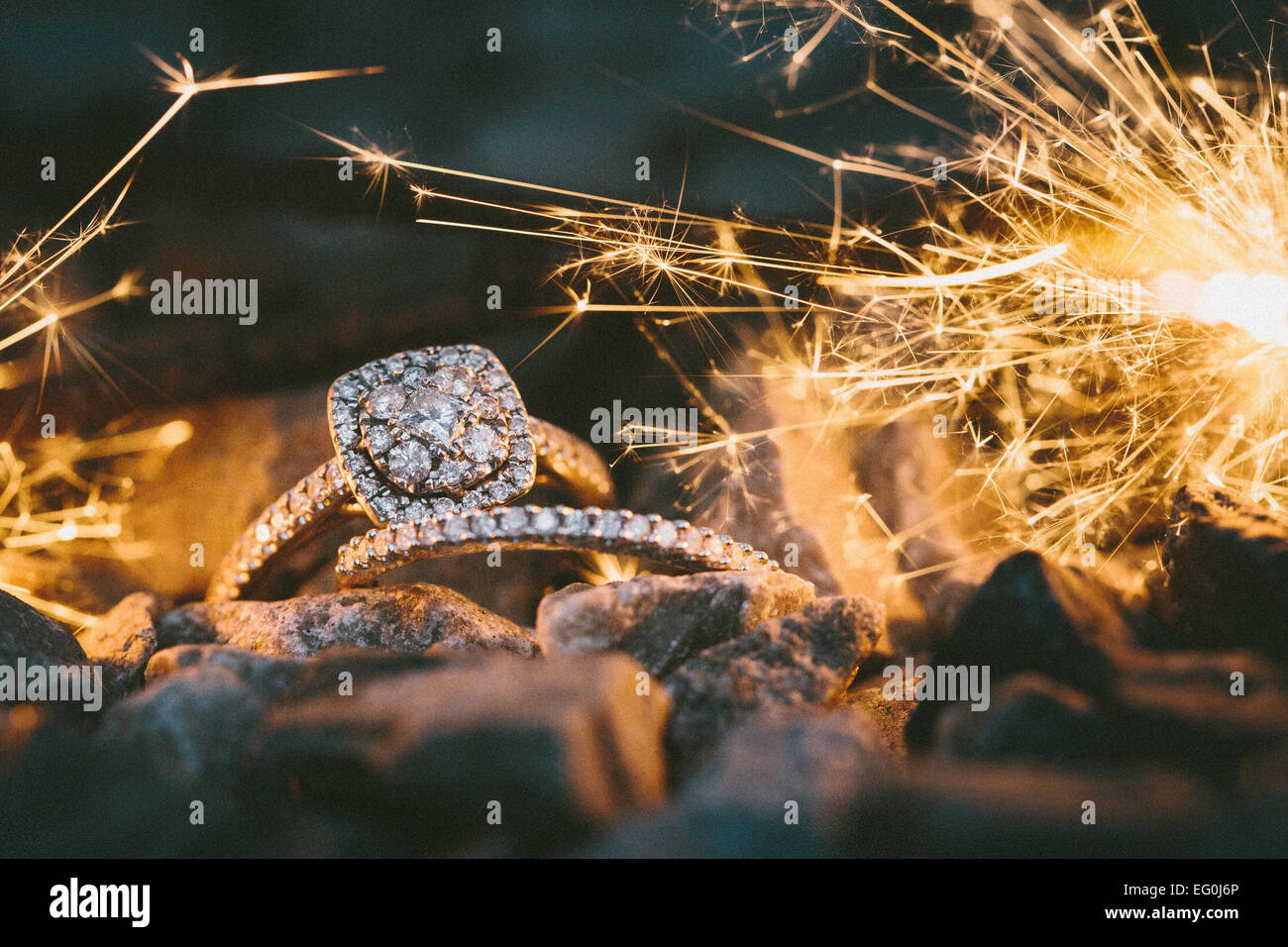 Wedding Rings hang on a sparkler as it burns down illuminating the rings Stock Photo