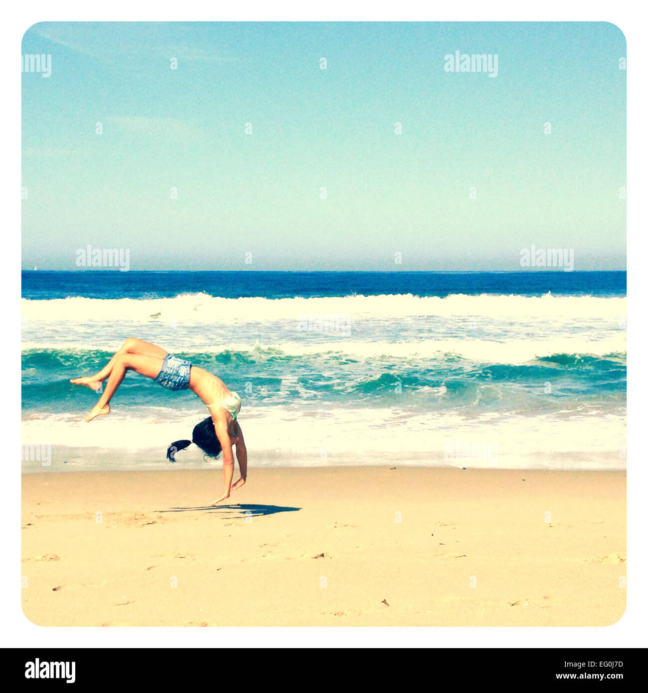 Girl doing a backflip on the beach - Stock Image