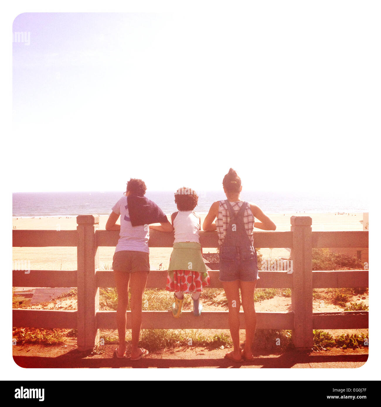 Three girls standing by a fence looking at the ocean, california, America, USA - Stock Image