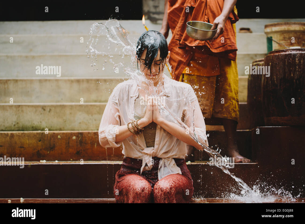 Cambodia, Buddhist monk water blessing young woman - Stock Image